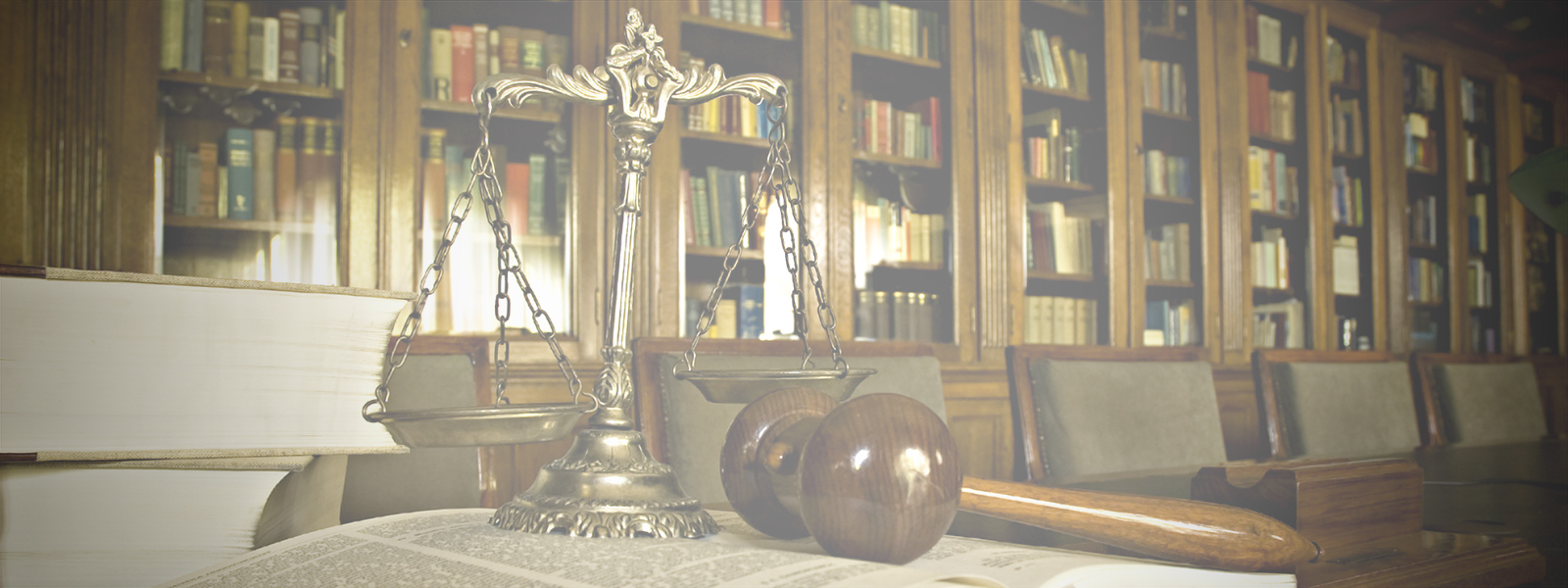 The scales of justice sit surrounded by a gavel and law books